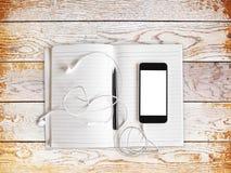 Téléphone portable vide avec des headhones et journal intime sur une table en bois Images stock