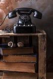 Téléphone poussiéreux de bakélite de vintage sur une boîte en bois à fruit avec le vieux livre Images libres de droits