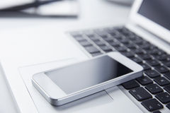 Téléphone se reposant sur un ordinateur portable Photographie stock