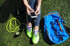 Téléphone sportif de participation de femme avec l'écran vide se reposant sur le gree Photographie stock libre de droits
