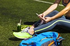 Téléphone sportif de participation de femme avec l'écran vide se reposant sur le gree Images stock