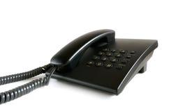 Téléphone stationnaire noir sur un fond blanc photographie stock libre de droits