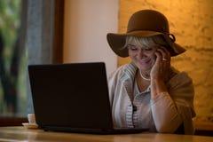 Téléphone supérieur de sourire de participation de dame Images libres de droits