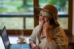 Téléphone supérieur de sourire de participation de femme Image stock
