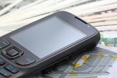 Téléphone sur l'argent comptant Photo stock