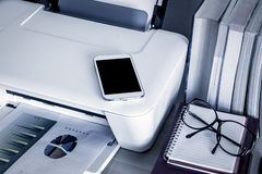 Téléphone, téléphone portable, téléphone intelligent sur l'imprimante avec des livres images libres de droits