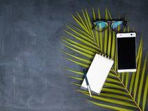 Téléphone, verres et carnet avec le stylo sur le tableau noir Photos stock
