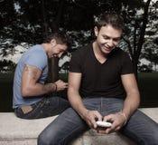 téléphones d'hommes jouant leurs deux Images stock