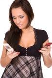 téléphones intéressants mobiles deux de fille caucasienne Images stock