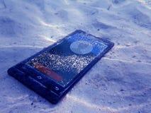 Téléphones portables sur le sable sous l'eau de mer images libres de droits