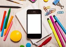 Téléphonez avec l'écran vide sur la table avec des outils de bureau Photo stock