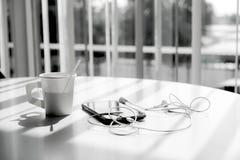Téléphonez avec les écouteurs et la tasse de café sur le bureau de table Photographie stock