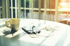 Téléphonez avec les écouteurs et la tasse de café sur le bureau de table Photos libres de droits