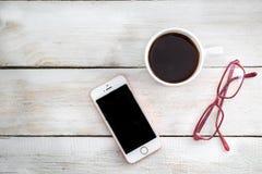 Téléphonez, des verres pour la vision et une tasse de café sur une table en bois Photos libres de droits