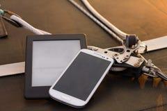 Téléphonez et marquez sur tablette sur un bateau au coucher du soleil Photo libre de droits