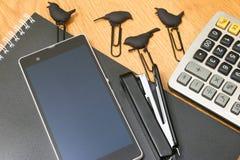 Téléphonez la calculatrice de fond et l'agrafeuse et les agrafes sur un bloc-notes Image libre de droits