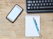 Téléphonez le stylo et le clavier de feuille de coffe sur le bureau Photographie stock libre de droits