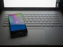 Téléphonez se reposer sur l'ordinateur portable avec le site de bureau de Facebook se reposant sur le Sc photos stock