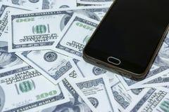 Téléphonez sur le fond de cent billets d'un dollar photographie stock