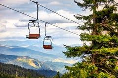 Télésiège allant au-dessus des arbres pendant l'été sur la montagne carpathien photos stock