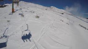 Télésiège de longueur avec des skieurs se déplaçant au dessus de la montagne dans un jour ensoleillé merveilleux clips vidéos