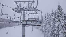 Télésiège vide en montagnes aux chutes de neige lourdes dans le mouvement clips vidéos