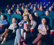 Téléspectateurs de sourire intéressés au film, se reposant dans le cinéma photos libres de droits