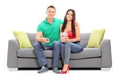 Télévision de couples et maïs éclaté de observation de consommation Photographie stock libre de droits
