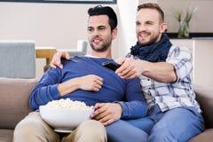 Télévision de observation de couples gais avec du maïs de bruit Image libre de droits