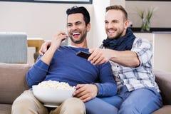 Télévision de observation de couples gais avec du maïs de bruit Photo stock