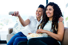 Télévision de observation de couples lesbiens avec un bol de maïs éclaté Photographie stock libre de droits