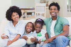 Télévision de observation de famille heureuse mangeant du maïs éclaté Images libres de droits