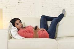 Télévision de observation de femme au film appréciant enthousiaste heureux de comédie de divan de sofa Photographie stock