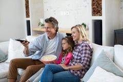 Télévision de observation de sourire de famille tout en ayant le maïs éclaté dans le salon Photographie stock libre de droits