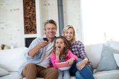 Télévision de observation de sourire de famille tout en ayant le maïs éclaté dans le salon Photo libre de droits