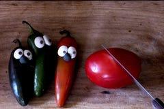 Témoins tomate et piments sur l'ensemble de Halloween de conseil en bois photos libres de droits