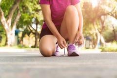 Tênis de corrida - close up da mulher que amarra laços de sapata Esporte fêmea imagens de stock