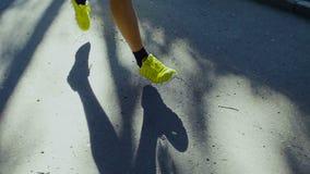 Tênis de corrida do homem que movimentam-se fora na estrada filme