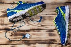 Tênis de corrida e leitor de mp3 em um fundo de madeira do assoalho fotos de stock royalty free