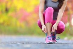 Tênis de corrida - mulher que amarra o close up dos laços de sapata de Imagens de Stock