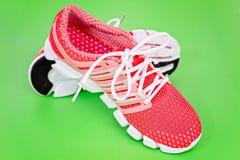 Tênis de corrida novo, sapatilha ou instrutor alaranjado e branco em b verde Fotos de Stock Royalty Free