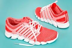 Tênis de corrida novo, sapatilha ou instrutor alaranjado e branco em vagabundos azuis Fotografia de Stock