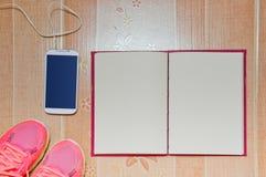 Tênis de corrida, telefone esperto, e caderno no fundo marrom Conceito do planeamento Foto de Stock Royalty Free
