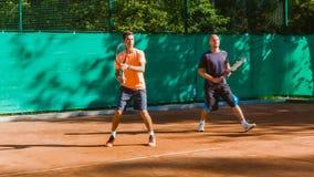 Tênis de treinamento ou de ensino do jogo em uma corte exterior Treinamento de jogadores dos esportes profissionais video estoque