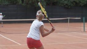 Tênis, menina do adolescente do jogador dos esportes com os rivais que batem a raquete na passagem da bola através da rede entre  filme