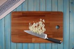 Tête d'oignon noir sur un conseil en bois pour couper des légumes image stock
