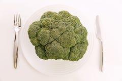 Tête de brocoli cru d'un plat dinant blanc photographie stock