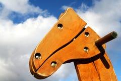 Tête de cheval en bois de balançoir contre les cieux nuageux Image libre de droits