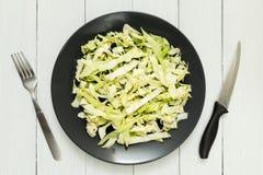 Tête de chou organique frais d'un plat, d'un couteau et d'une fourchette Table en bois blanche images stock