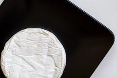 Tête de fromage de camembert ou de brie dans le plat de place noire, minimalisme Vue supérieure, l'espace de copie Images libres de droits
